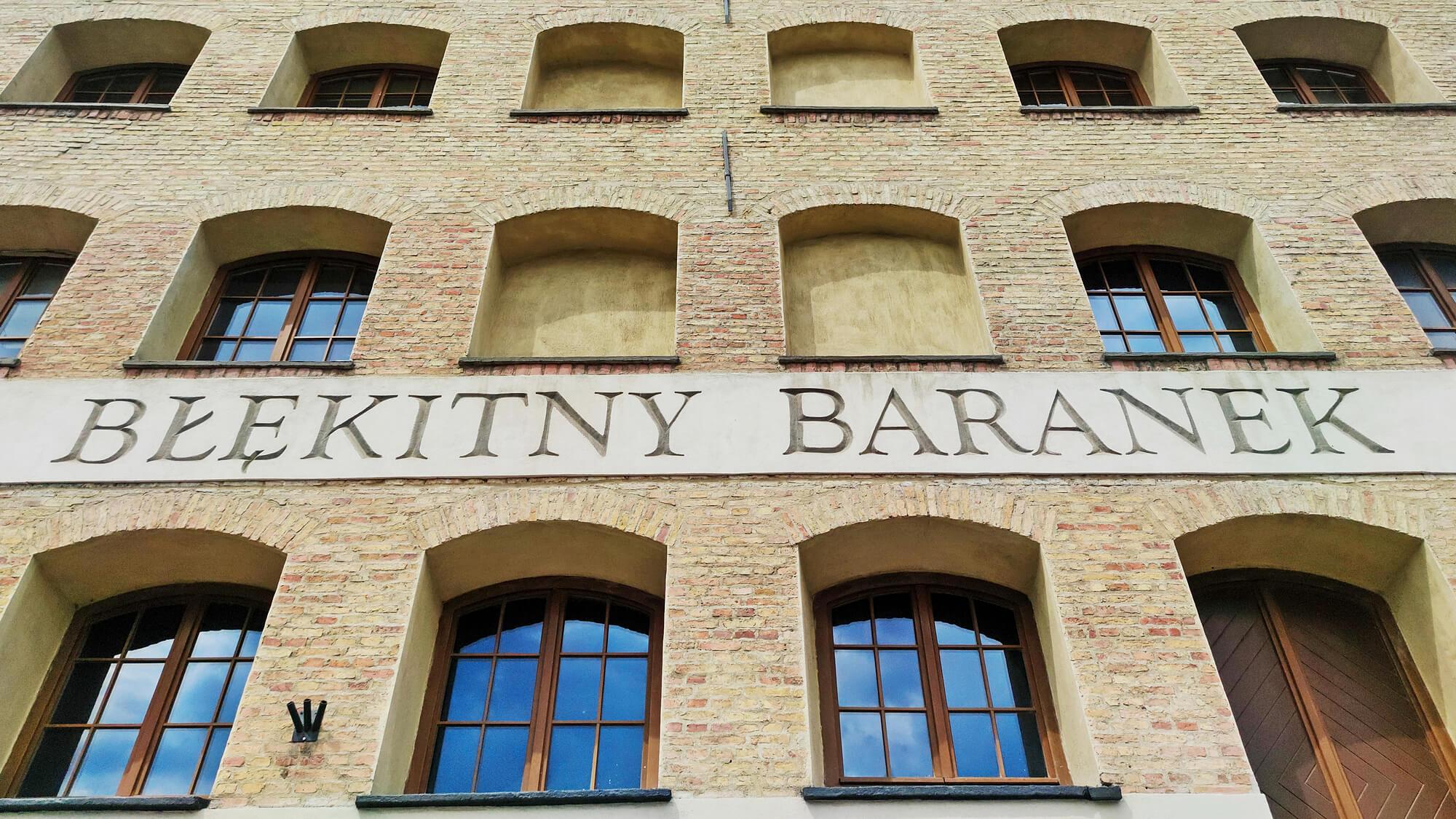 """Fragment fasady zabytkowego spichlerza z trzema rzędami okien i napisem """"Błękitny Baranek""""."""