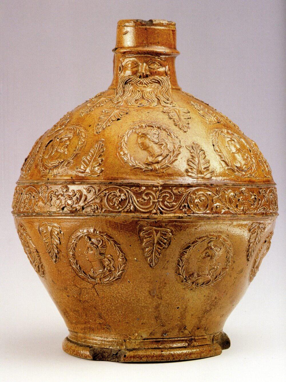 Brązowy, pękaty dzban, bogato dekorowany; na krótkiej szyjce naczynia widać wizerunek brodacza.