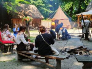 Ludzie siedzący przy ognisku pośrodku zrekonstruowanej wczesnośredniowiecznej osady.